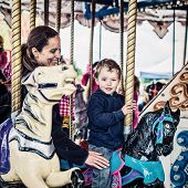 pic of amusement park rides  - A happy mother and son are riding on a carousel together having fun at an amusement park - JPG