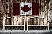 image of bench  - Two rustic wooden log benches sit side by side outdoor against a building wall made of wooden siding with a Canada flag hanging on the wall just above the benches - JPG