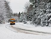 pic of driving school  - A school bus drives down a snow covered rural country road lined with snow covered trees after a snow storm during the winter season - JPG