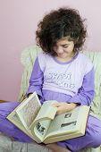 stock photo of ten years old  - Ten year old girl in pajamas and old encyclopedia - JPG