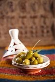 marinated Olives in tajine bowls with moroccan  ornament on wood, shallow dof