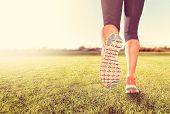 an athletic pair of legs on grass during sunrise or sunset - he