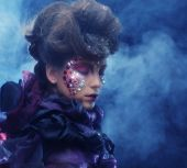 portrait of woman with artistic make-up in blue smoke