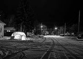 picture of igloo  - Small igloo lit up at night beside a snow covered street at night