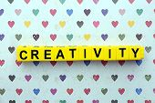 Creativity motto by alphabet letters on surface with hearts on background