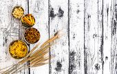 stock photo of kindness  - different kinds ofdifferent kinds of pasta on textured wooden table - JPG