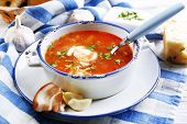 Ukrainian beetroot soup - borscht, on blue napkin, on wooden background