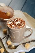 Cup of hot coffee with marshmallow on cutting board with sieve of cocoa, lump sugar and sticks of vanilla on color wooden table background