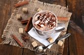 Cup of hot coffee with marshmallow on burlap cloth with lump sugar, sticks of cinnamon and star anise on rustic wooden planks background