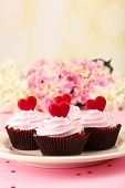 Delicious Valentine Day cupcakes on pink background