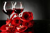Composition with red wine in glasses, red rose and decorative heart on dark background