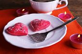 Cookies in form of heart in plate with cup of coffee and candles on napkin, on rustic wooden planks background