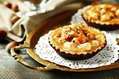 Mini cakes with nuts on napkin on wooden background