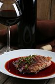 Grilled steak in wine sauce with glass of wine on wooden background