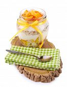 Healthy breakfast - yogurt with  fresh peach and muesli served in glass jar on wooden tray, isolated on white