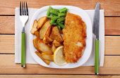 Breaded fried fish fillet and potatoes with asparagus and lemon on plate with napkin and cutlery on wooden planks background