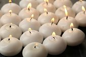 Burning candles on wooden table close-up