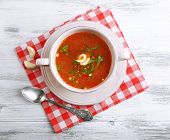 Ukrainian beetroot soup - borscht, on napkin, on wooden background