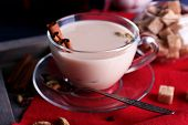 Black tea with milk and lump sugar on wooden tray with napkin and color wooden planks background