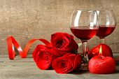 Composition with red wine in glasses, red roses and decorative heart on wooden background