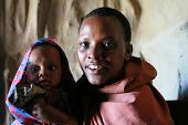 Portrait Of Black Woman With Baby Inside Huts Tribe Maasai.