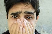 image of tragic  - Portrait of a young man crying at some loss.