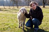 Young Woman With Small Lamb Look Happy