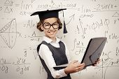 Smiling smart schoolgirl in big glasses and academic hat performs the task at the blackboard with a laptop. Education.