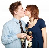Young Couple In Love Kiss, Celebrating A Date With Glasses Of Champagne, Isolated On White Backgroun
