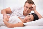 pic of early-man  - Young couple lying in white bed early in the morning - JPG
