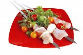 raw  chicken kebabs served with cherry and greenery