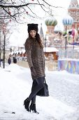 Portrait in full growth of a beautiful stylish young woman on the background Red Square, Moscow Kremlin, Russia