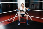 Boxing woman sitting alone in arena at the gym