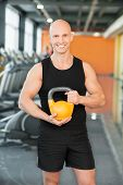 Man doing exercise with kettlebell in gym