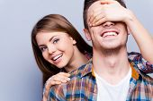 picture of peek  - Beautiful young women covering eyes of her boyfriend and peeking out his back while standing against grey background - JPG