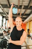 Portrait of young fit man lifting a kettlebell