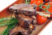 meat portion : ribs on plate served with fresh cherry tomatoes and raw vegetables and chives