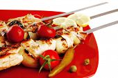 fresh roast chicken shish kebab on red platter