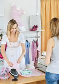 foto of cash register  - Positive saleswoman packing clothes in a bag in a clothes store - JPG