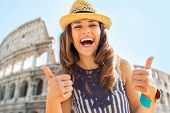 Portrait Of Happy Young Woman Showing Thumbs Up In Front Of Colosseum In Rome, Italy
