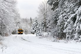 foto of driving school  - A school bus drives down a snow covered rural country road lined with snow covered trees after a snow storm during the winter season - JPG
