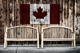 image of red siding  - Two rustic wooden log benches sit side by side outdoor against a building wall made of wooden siding with a Canada flag hanging on the wall just above the benches - JPG