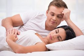 picture of early 20s  - Young couple lying in white bed early in the morning - JPG