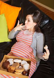 stock photo of finger-licking  - Pregnant woman with box of donuts licking her fingers - JPG