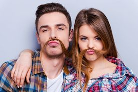 foto of moustache  - Beautiful young loving couple making fake moustache from hair while standing against grey background - JPG