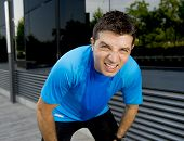 picture of breath taking  - young attractive man leaning exhausted after running session sweating taking a break to recover in urban street summer background - JPG