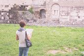 image of marsala  - Tourist with map getting around ancient roman ruins in Rome old town heritage of early italian history now famous travel destination for tourists. Marsala toned image decontrasted. ** Note: Visible grain at 100%, best at smaller sizes - JPG