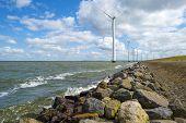 foto of wind-farm  - Wind farm in water along a dike in spring - JPG