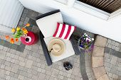 picture of paving  - Taking a relaxing tea break in a deep seating patio set with a comfortable armchair flanked by colorful spring flowers with a sunhat and garden shoes on a brick paved outdoor patio overhead view - JPG