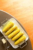 image of serving tray  - Delicious tray of cooked corncobs or sweet corn served with salt and butter for a healthy snack or lunch overhead view on a table with copyspace over a hardwood parquet floor - JPG